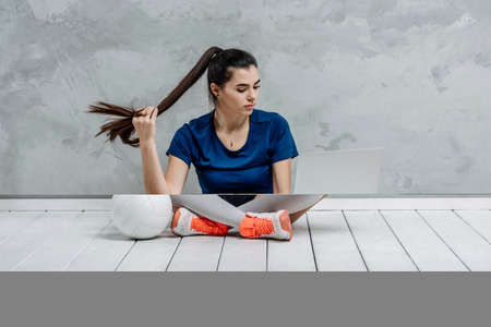 Young girl doing exercises with volleyball ball watching online tutorials on laptop. A sports coach leads an online lesson. Online workout concept. Vintage color filter