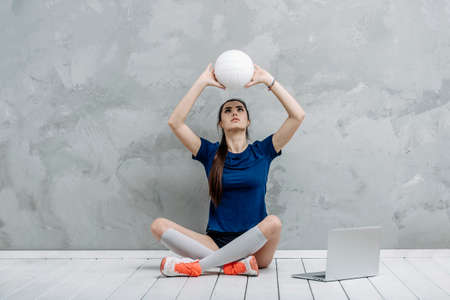 Young girl doing exercises with volleyball ball watching online tutorials on laptop. A sports coach leads an online lesson. Online workout concept. Vintage color filter 写真素材 - 158852734