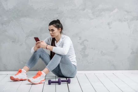 Young woman using smartphone during workout at home in the living room. Online personal trainer or on mobile phone. Workout online concept. Vintage color filter 写真素材 - 158852455