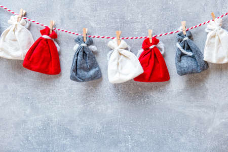 Advent Calendar on grey wall background. Christmas bags hanging on rope on grey background