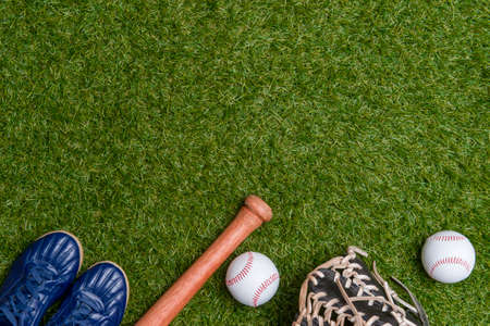 Baseball bat,shoes, glove and ball on green grass field. Sport theme background with copy space for text and advertisment