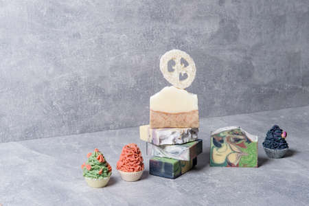 Handmade soaps and loofah sponges on grey background. Eco lifestyle concept.