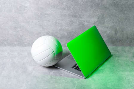 White Volleyball ball and grey laptop on grey background. Online workout concept