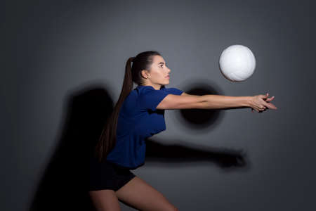 Volleyball girl hold and kick ball in blue costume on dark wall background. Player doing sport workout at home. Sport and recreation concept 免版税图像