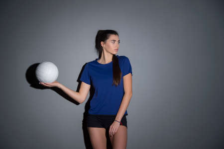 Volleyball girl hold and kick ball in blue costume on dark wall background. Player doing sport workout at home. Sport and recreation concept 写真素材