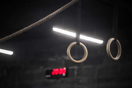 Close-up low angle view of gymnastic ring hanging in gym. Sport equipment element for gymnastics. Workout online concept 写真素材