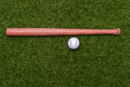 tBaseball bat and ball on green grass field.  Sport theme background with copy space for text and advertisment