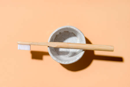 Bamboo toothbrush in holder on beige background. Zero waste concept