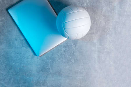 ttWhite Volleyball ball and grey laptop on grey background. Online workout concept