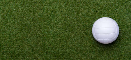 White volleyball ball on green grass. Team sport concept