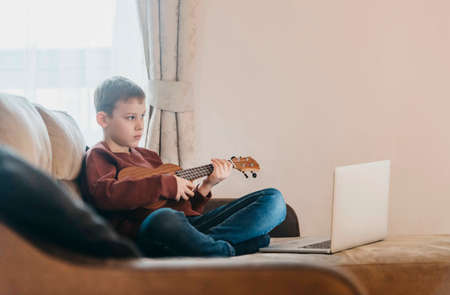 Boy playing ukulele and watching online course on laptop while practicing at home. Online training, online classes.Vintage color filter 写真素材