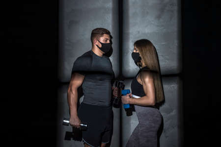 Two sports persons wearing protective face masks and training in gym. Strength and motivation