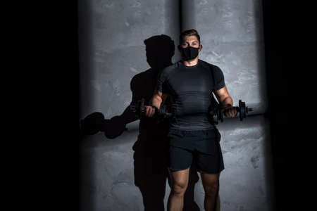 Male athlete wearing protective face mask and training with dumbbell in gym. Workout in gym after pandemic