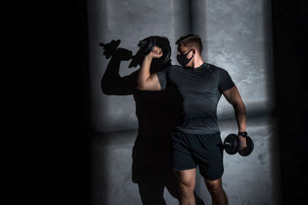 Male athlete wearing protective face mask and training with dumbbell in gym. Coronavirus world pandemic and sport theme.