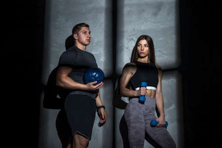 Attractive young couple in sport wear doing exercise in the gym. Strength and motivation