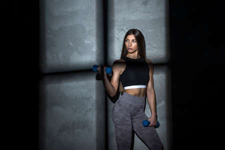 Sporty woman does the exercises with dumbbells on dark background. Strength and motivation 写真素材