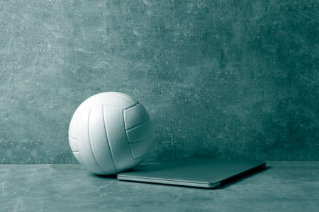 White Volleyball ball and grey laptop on grey background. Online workout concept. Green color filter