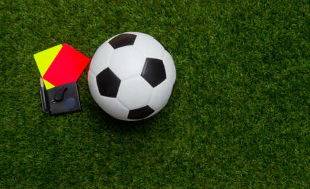 Football soccer referee equipment on green grass background. Top view, space for your text. 写真素材