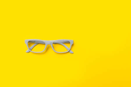 Grey glasses on a yellow background. Top view, space for your text.