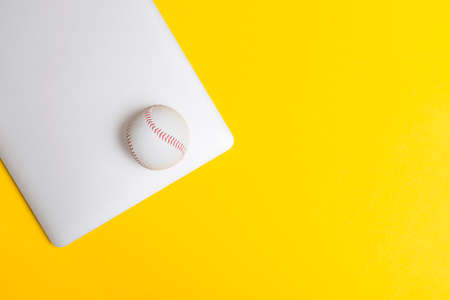 Baseball ball and grey laptop on yellow background. Online workout concept. Top view, space for your text 写真素材
