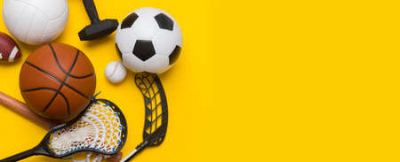 Assorted sports equipment including a soccer ball, volleyball, baseball, american football, lacrosse and hockey on a blue background. Top view, space for your text