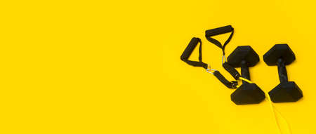 Black dumbbells and elastic exercise band for fitness training on yellow background. Top view, space for your text. 写真素材