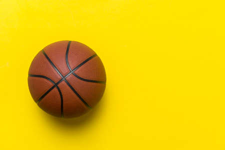 Close up of brown basketball ball isolated on yellow. Sport team concept. Top view, space for your text 写真素材