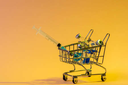 Shopping trolley with syringes, injections, vaccines on yellow background. Vaccination concept