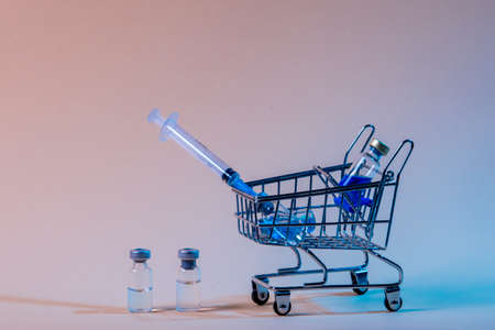 Shopping trolley with syringes, injections, vaccines on blue background. Vaccination concept