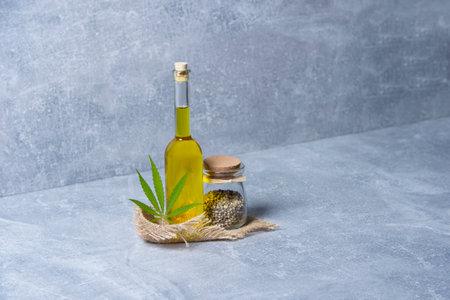 Green marijuana leaf, hemp seeds and cannabis oil on grey background. Alternative medicine. Vegetarian food concept 写真素材