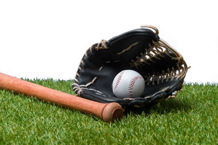 Baseball bat, glove and ball on green grass field.  Sport theme background with copy space for text and advertisment 写真素材