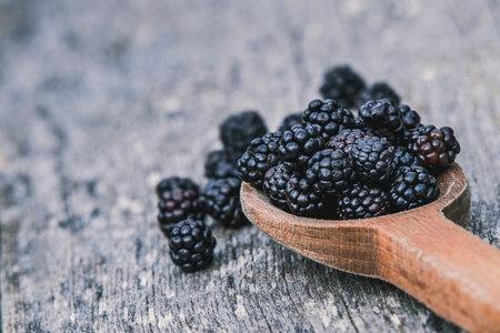 Ripe blackberries in wooden spoon on old wooden background