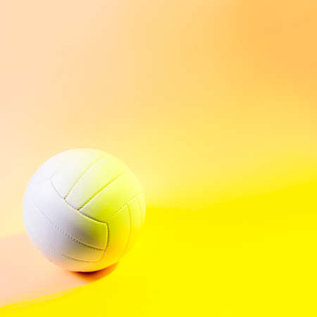 Volleyball ball on yellow background. Team sport concept