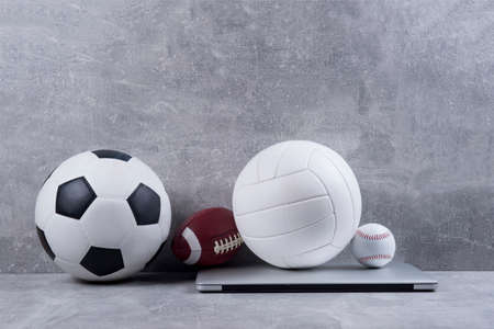 Soccer, volleyball, american football and baseball ball and grey laptop on grey background. Online workout concept 写真素材
