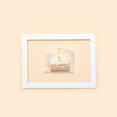 Handmade soap and loofah sponges in the frame on a beige background. Eco lifestyle concept.