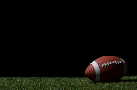 American football on green grass, on black background. Team sport concept