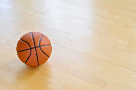 A basketball on the wooden floor as background. Team sport concept 写真素材