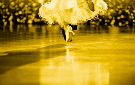 Man and woman dancer latino international dancing.  Ballroom dancing is a team sport. Yellow color filter