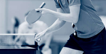 Close up of a man hands holding table tennis rocket and ball. Blue color filter