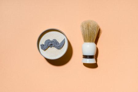 Shaving brush and shaving foam on camel color background. Spa organic foam. Zero waste concept