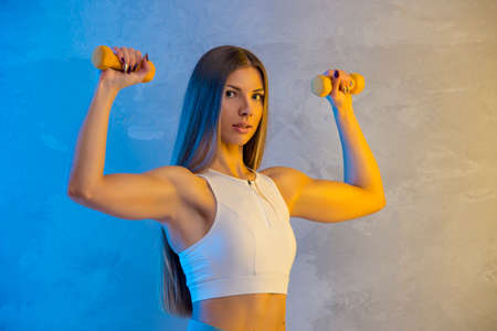 Fitness young woman working out with dumbbells isolated on neon light background. Online workout concept 写真素材