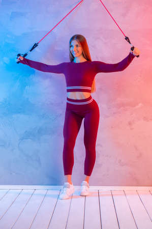 Athletic trainer with rubber resistance bands teaches group fitness and work out online training on a bright neon background. Sport online concept