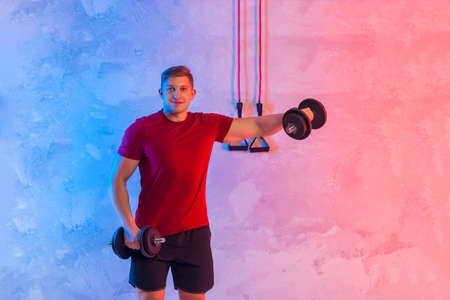 Athletic trainer with black dumbbells and rubber resistance bands teaches group fitness and work out online training on a bright neon background. Sport online concept 写真素材