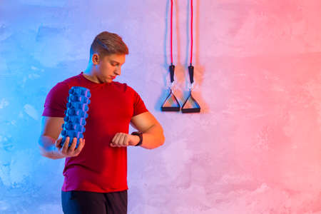 Athletic trainer with blue massager and rubber resistance on a bright neon background. Fitness man looking at her wrist watch. Interactive coach concept 写真素材