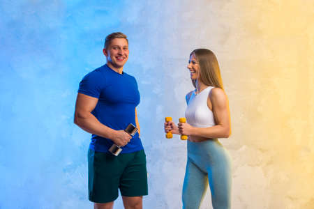Attractive young couple in sport wear doing exercise in the gym. Strength and motivation concept. Workout online theme