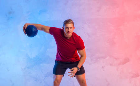 Muscular man exercise with medicine ball at health club. Fitness routine with exercise. Interactive coach concept 写真素材