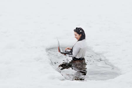 Girl with laptop in frozen lake ice hole. Woman hardening the body in cold water. Imagens