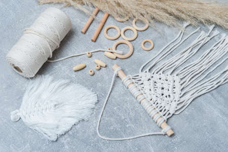 Macrame accessories on grey background. Creative hobby concept. Top view. Vintage color filter