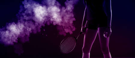 Tennis girl hold racket and ball on dark background. Player doing sport workout online. Sport and recreation concept. Neon color filter