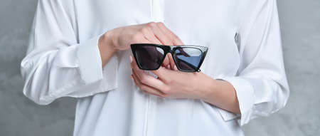 Midsection of woman holding sunglasses. Background for product display, banner, or mockup 免版税图像